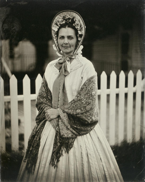 Wearing an outfit she made herself, Civil War reenactor Maegen Hensley poses in front of the Drum Barracks Civil War Museum in Los Angeles, California. Hensley is a member of the Historical Citizens Association, a nonprofit Southern California reenacting group that seeks to educate the public about American history. Wet-plate photograph.